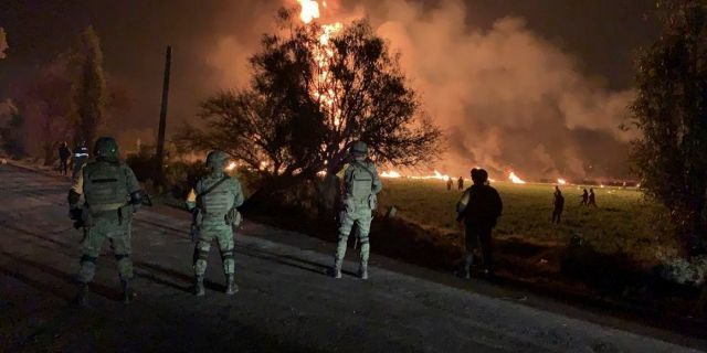 Mexican soldiers guard the area by an oil pipeline explosion in Tlahuelilpan, Hidalgo state, Mexico, Friday, Jan. 18, 2019. (Secretary of National Defense via AP)