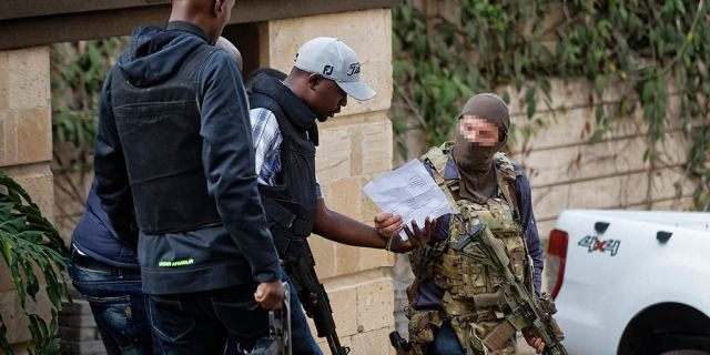 An unidentified member of Britain's SAS discusses with Kenyan security forces before entering to clear a building at a hotel complex in Nairobi, Kenya Tuesday, Jan. 15, 2019.
