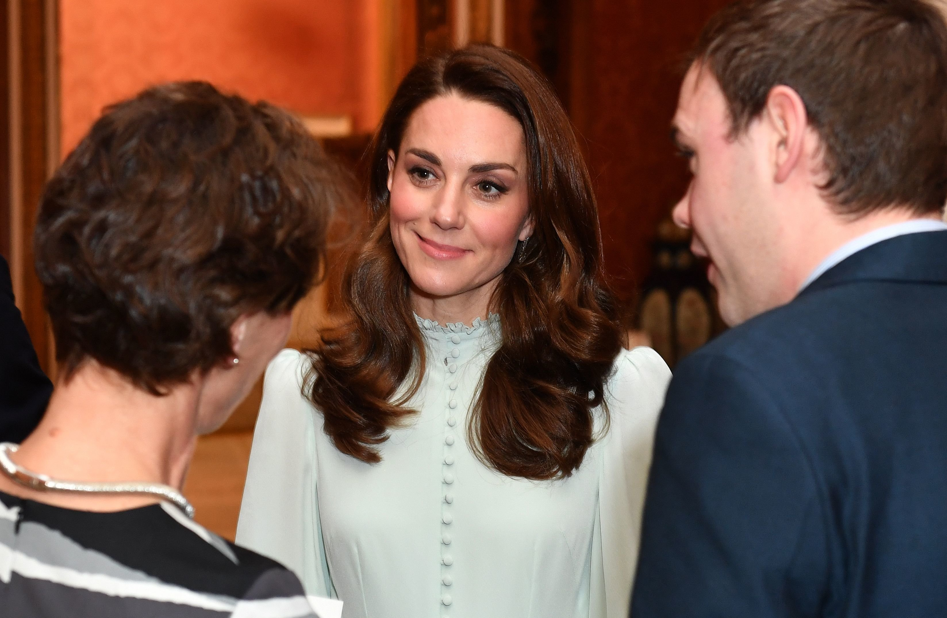 Catherine, Duchess of Cambridge, talks with guests as she attends a reception to mark the 50th Anniversary of the investiture