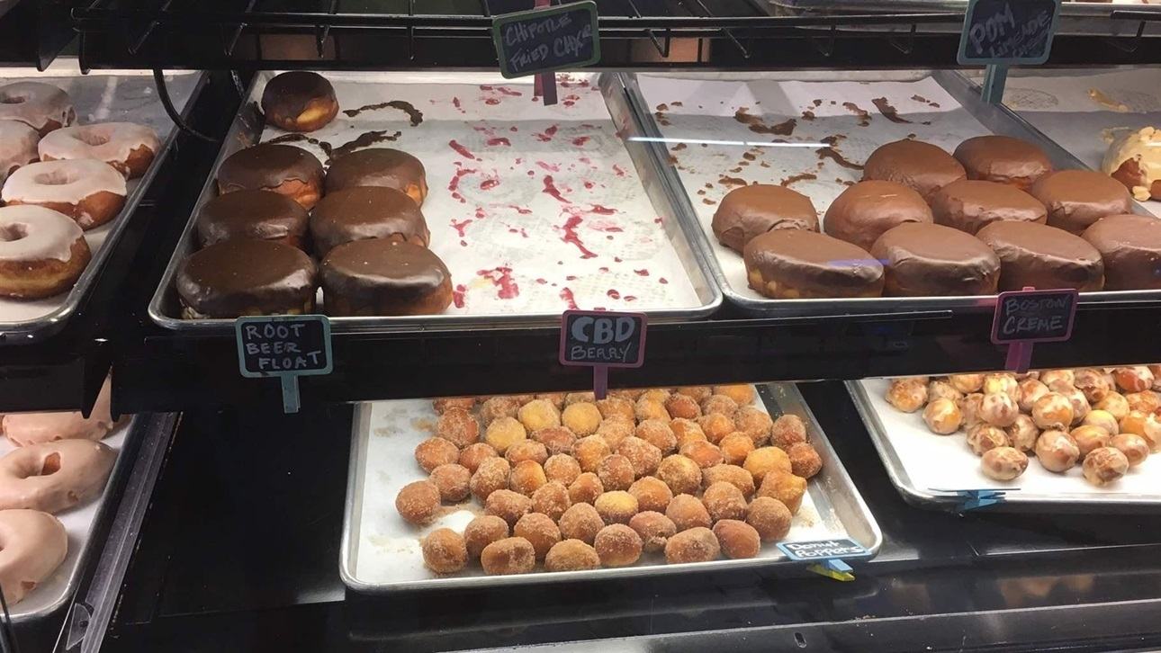 A rack of doughnuts for sale, including a sold-out tray for CBD doughnuts, at Glazed & Confuzed in Aurora, Colorado. Rest