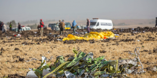 Parts of the plane wreckage with rescue workers at the crash site at Bishoftu, or Debre Zeit, outside Addis Ababa, Ethiopia, Monday, March 11, 2019, where Ethiopia Airlines Flight 302 crashed Sunday.