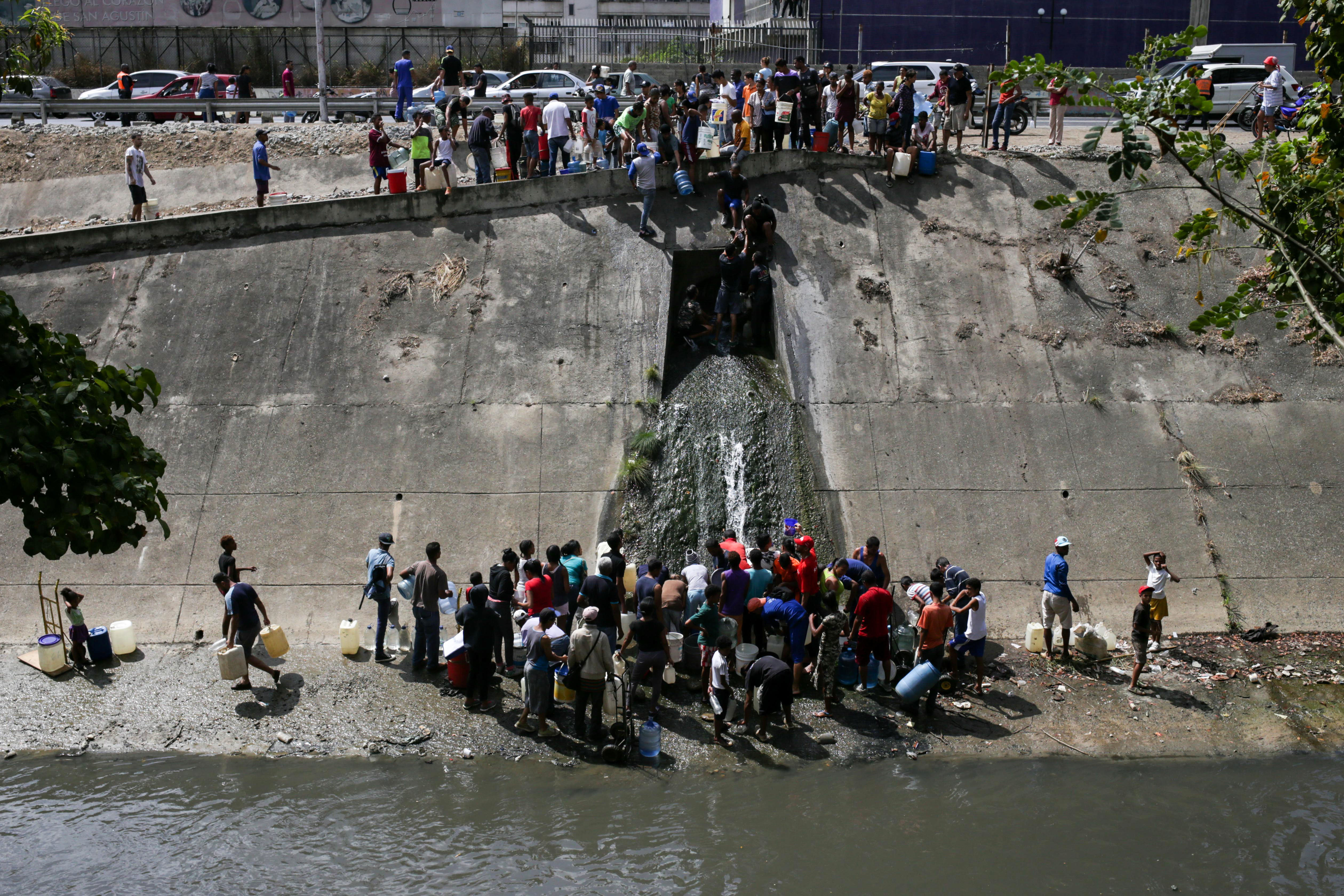 Venezuelans collect water flowing into a sewage canal from a broken pipe at the Guaire River in Caracas on March 11, 2019, as