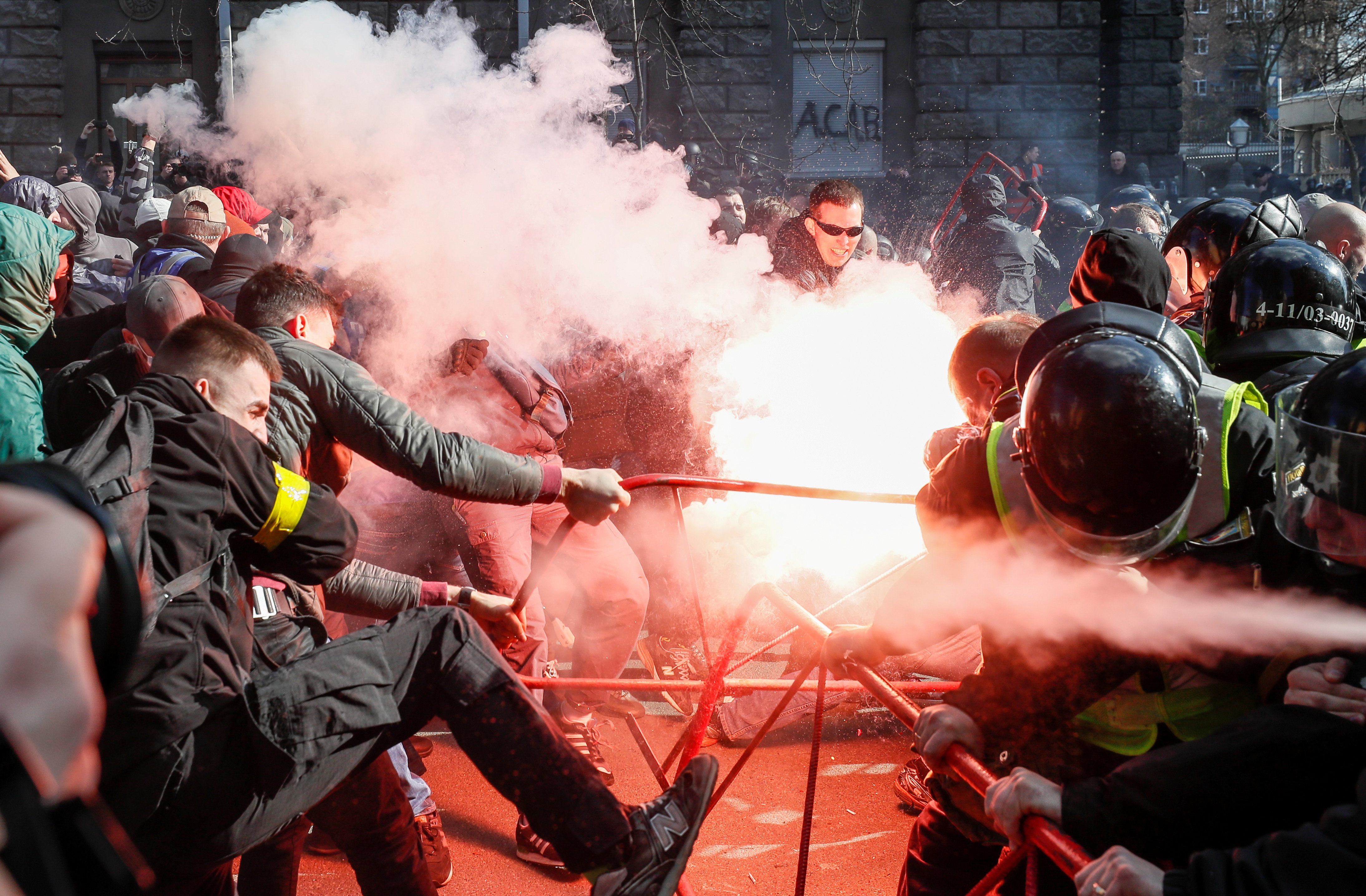 Members of Ukrainian nationalist parties scuffle with police officers during a rally to demand an investigation into the corr