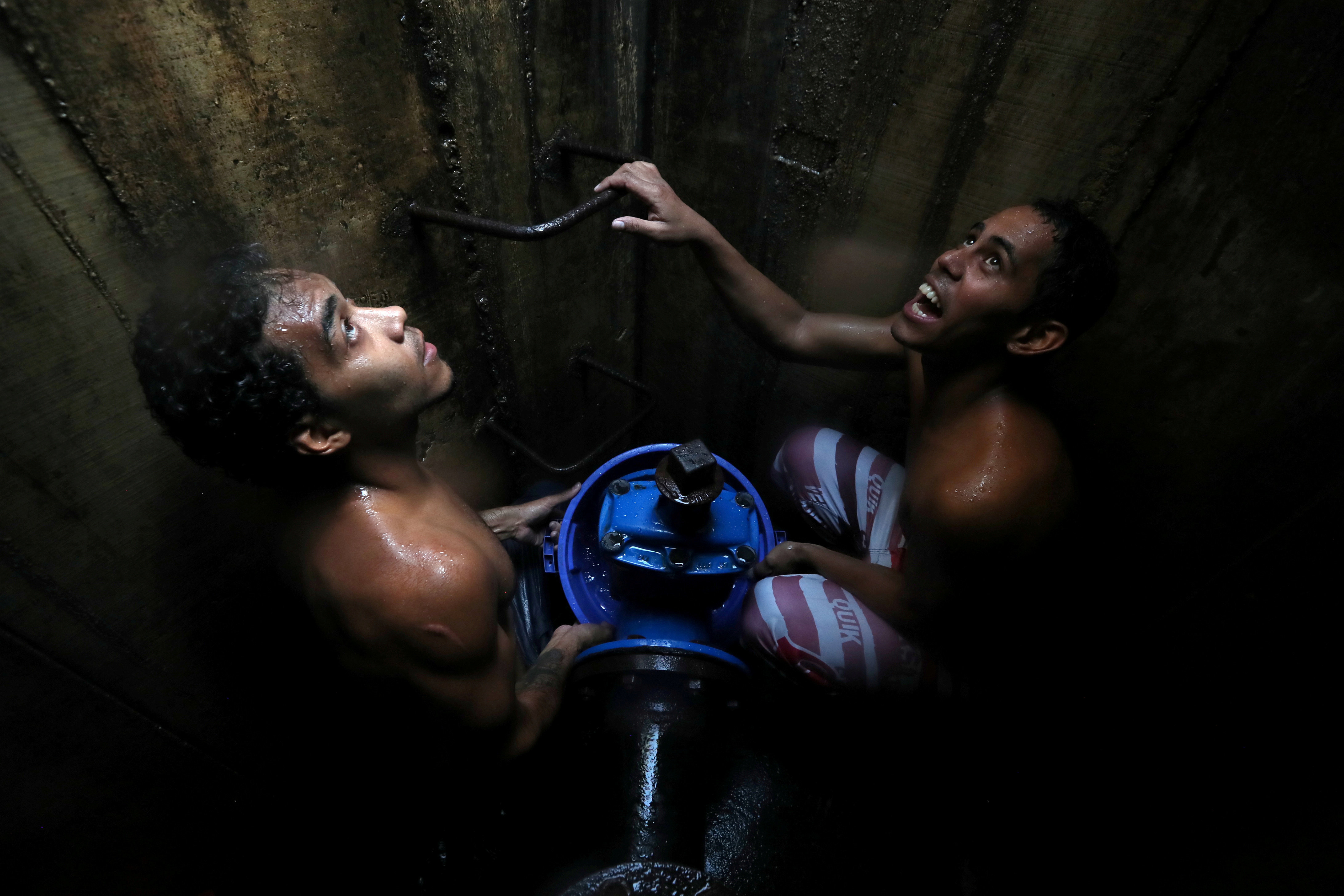Locals collect water from an underground water main pipeline in Caracas, Venezuela, on March 12, 2019.