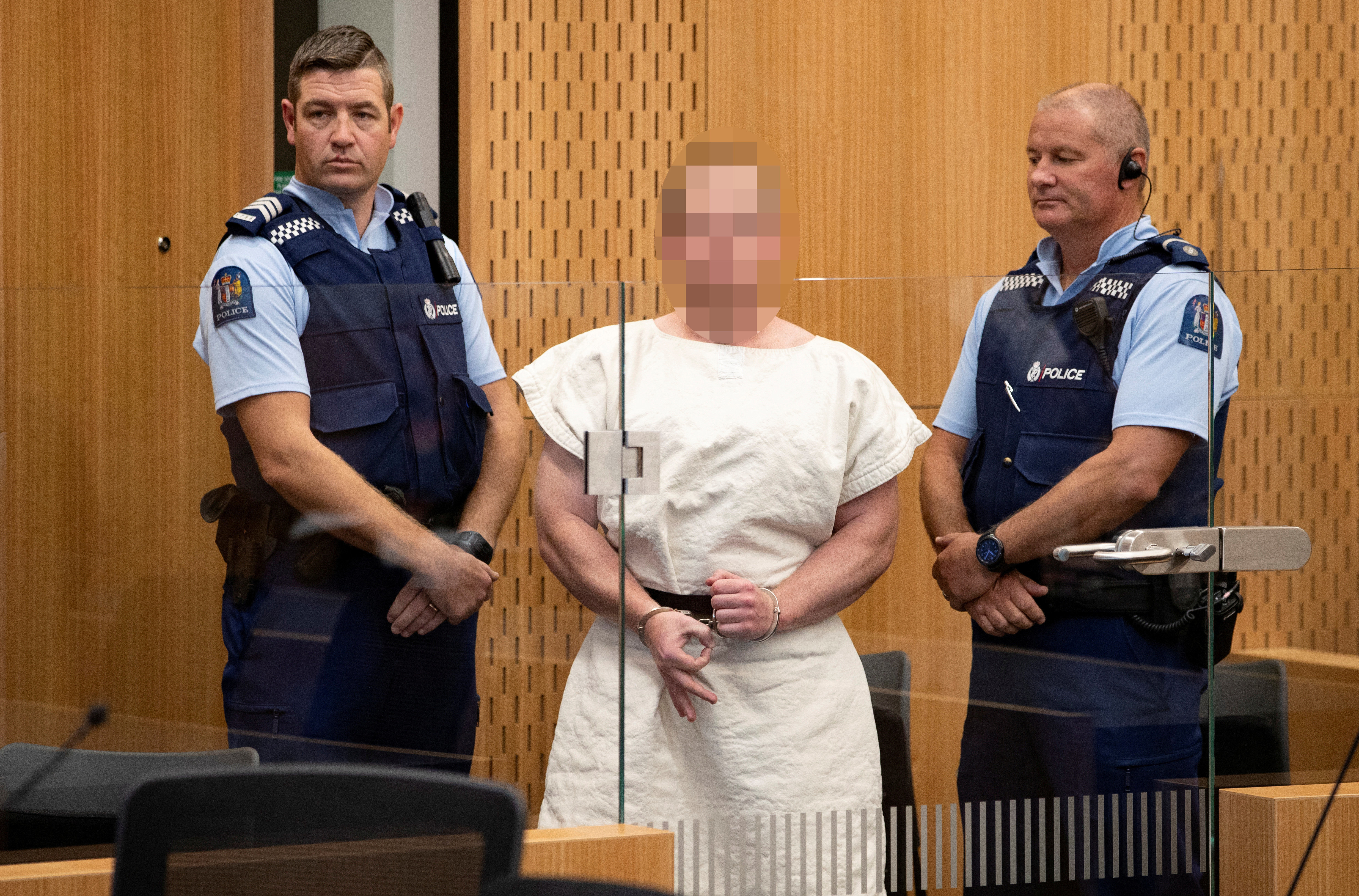 The suspect made a sign to the camera during his appearance in the Christchurch District Court on Saturday.