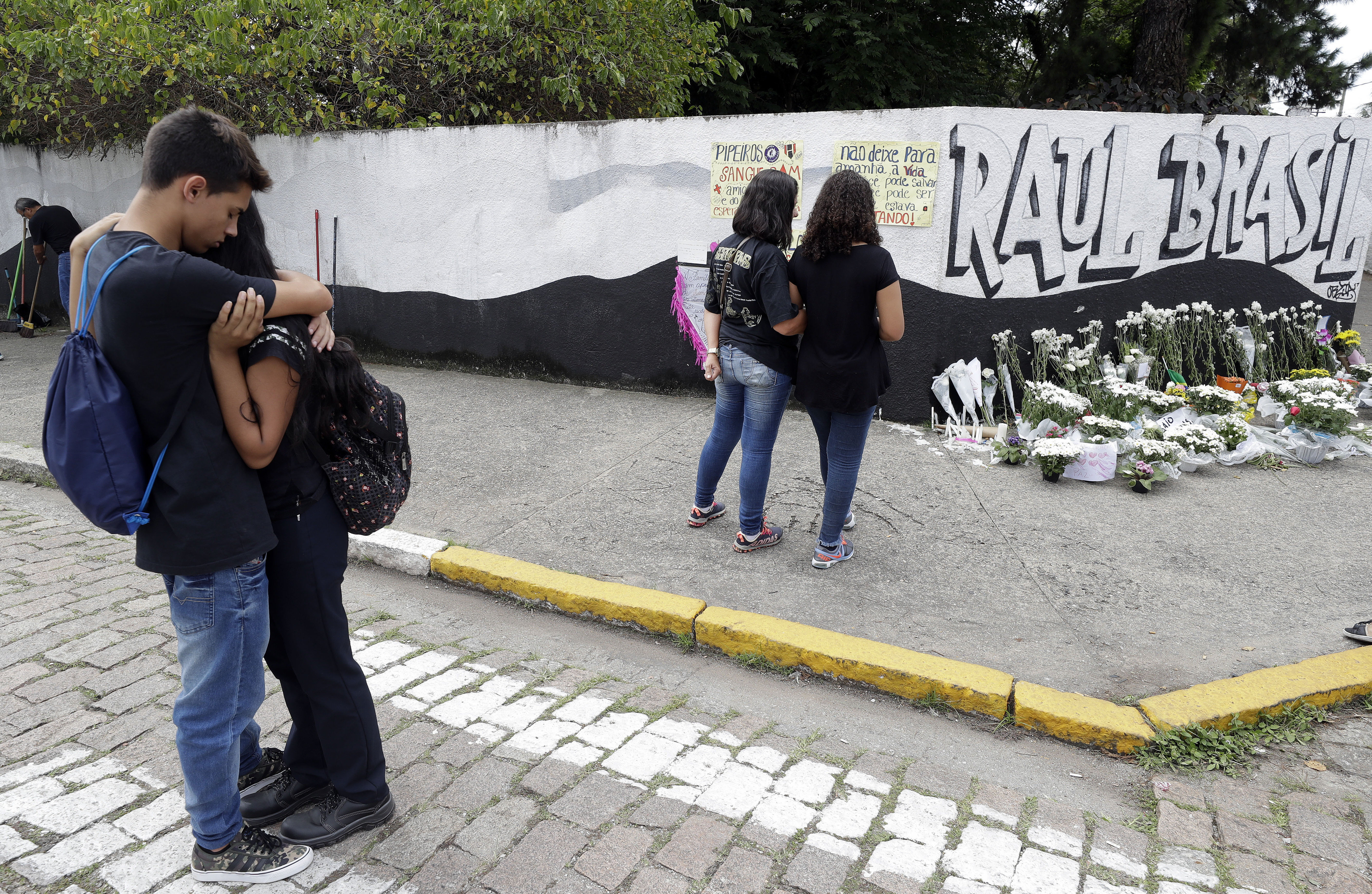 Students embrace outside the Raul Brasil state school one day after a mass shooting there in Suzano, Brazil, on March 14, 201