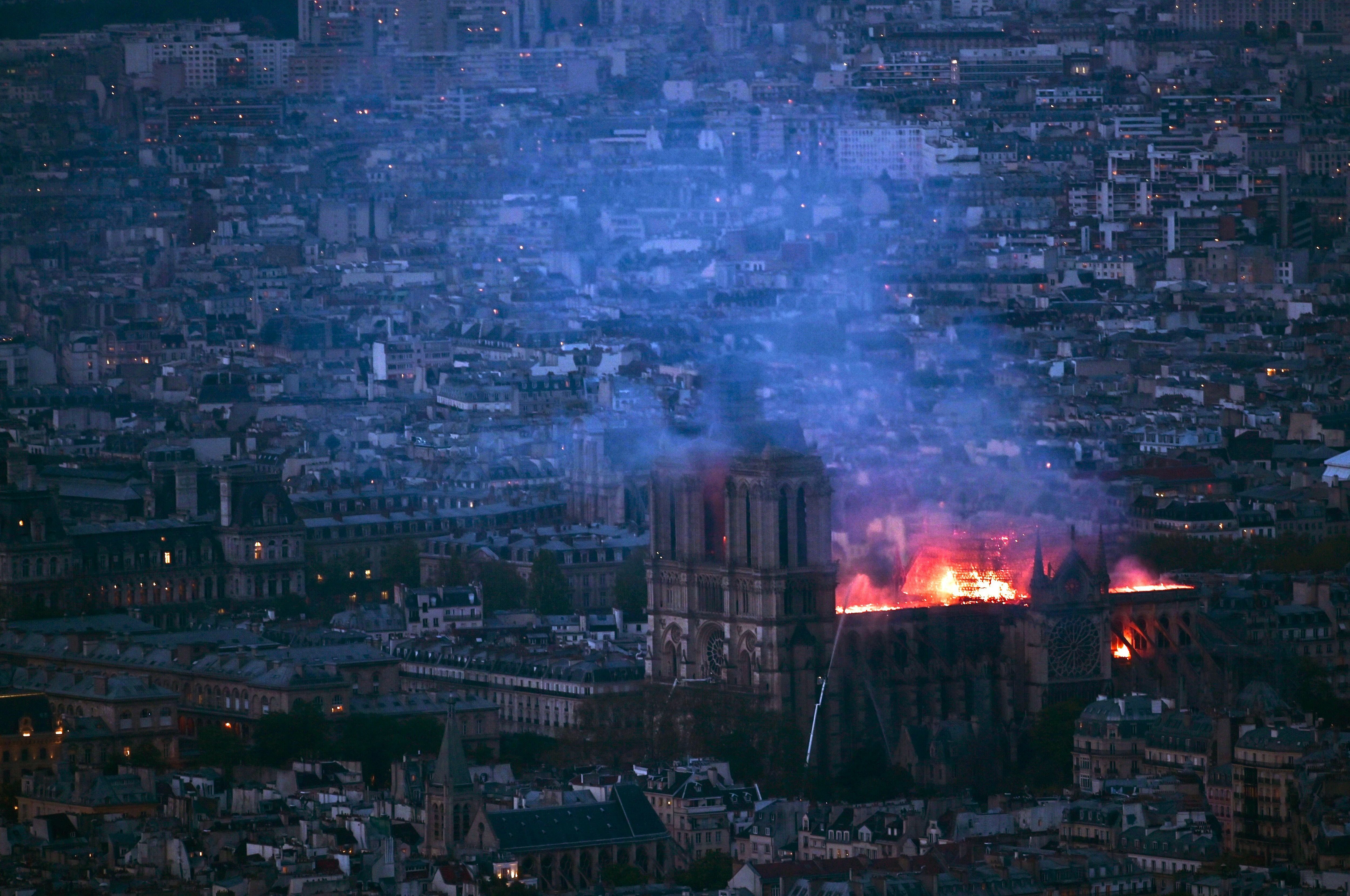 A view from Montparnasse Tower shows flames and smoke billowing from the roof of Notre Dame Cathedral in Paris.