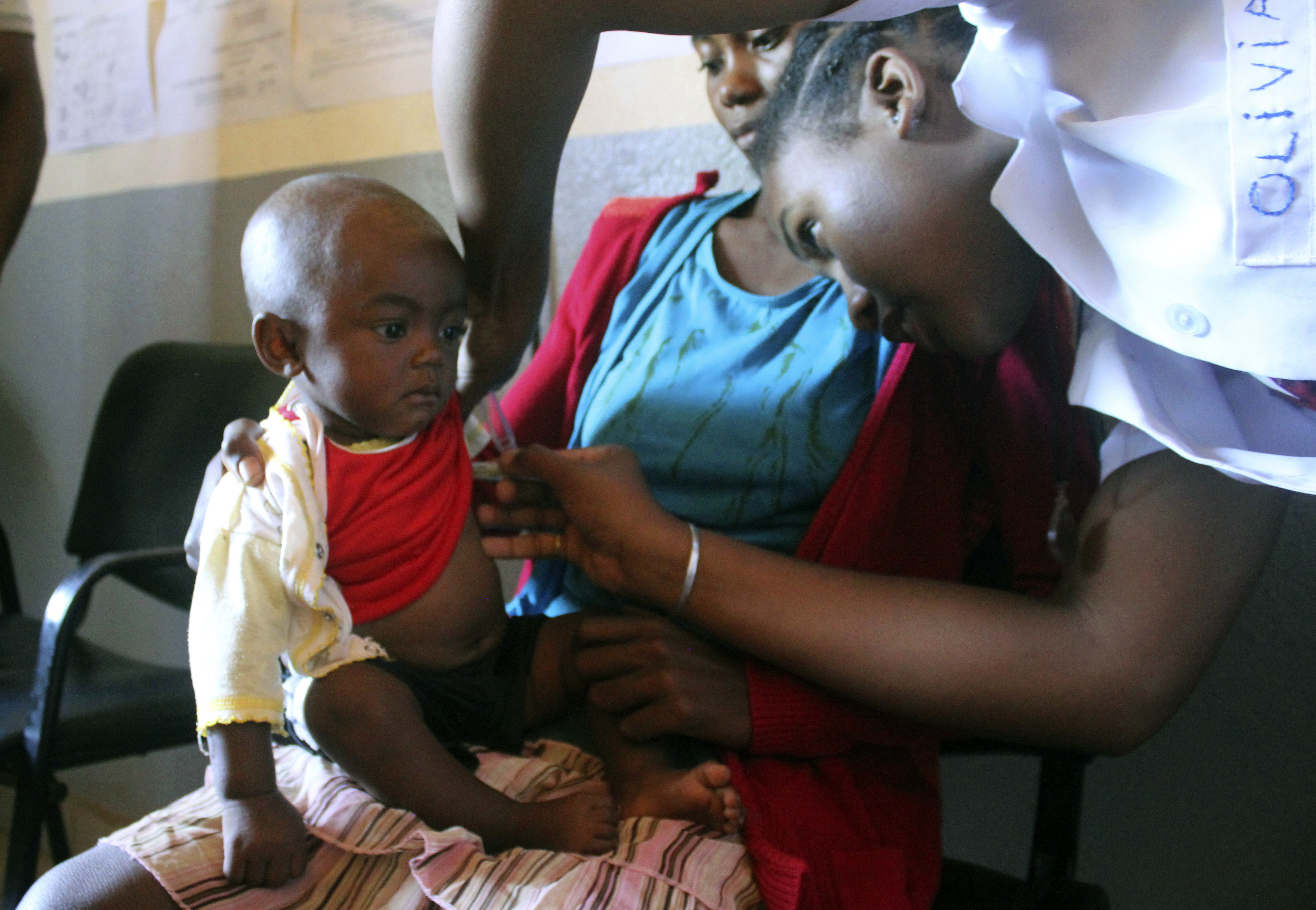 A volunteer nurse at a health care center in Larintsena, Madagascar, examines a 6-month-old who has measles while her mother,