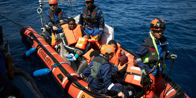 This April 3, 2019 photo shows migrants on a rubber dinghy rescued by the Sea-Eye rescue ship in the waters off Libya. The humanitarian ship Sea-Eye with 64 rescued migrants aboard was stuck at sea on Thursday as Italy and Malta refuse it safe harbor as their refusal set the stage for another Mediterranean standoff that can only be resolved if European governments agree to accept the asylum-seekers.
