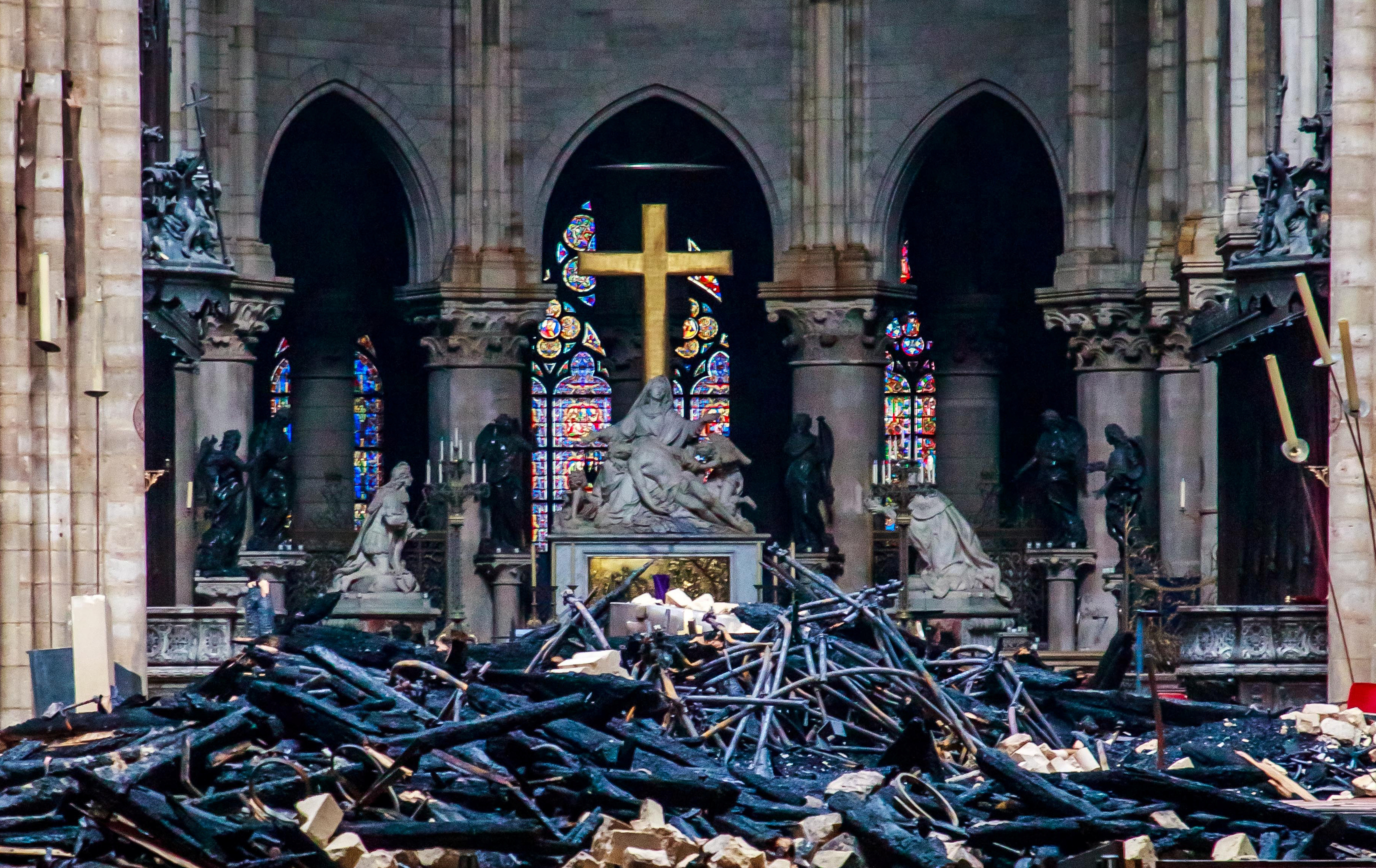 Blackened remains of Notre Dame's wooden roof framework lie on the cathedral floor.