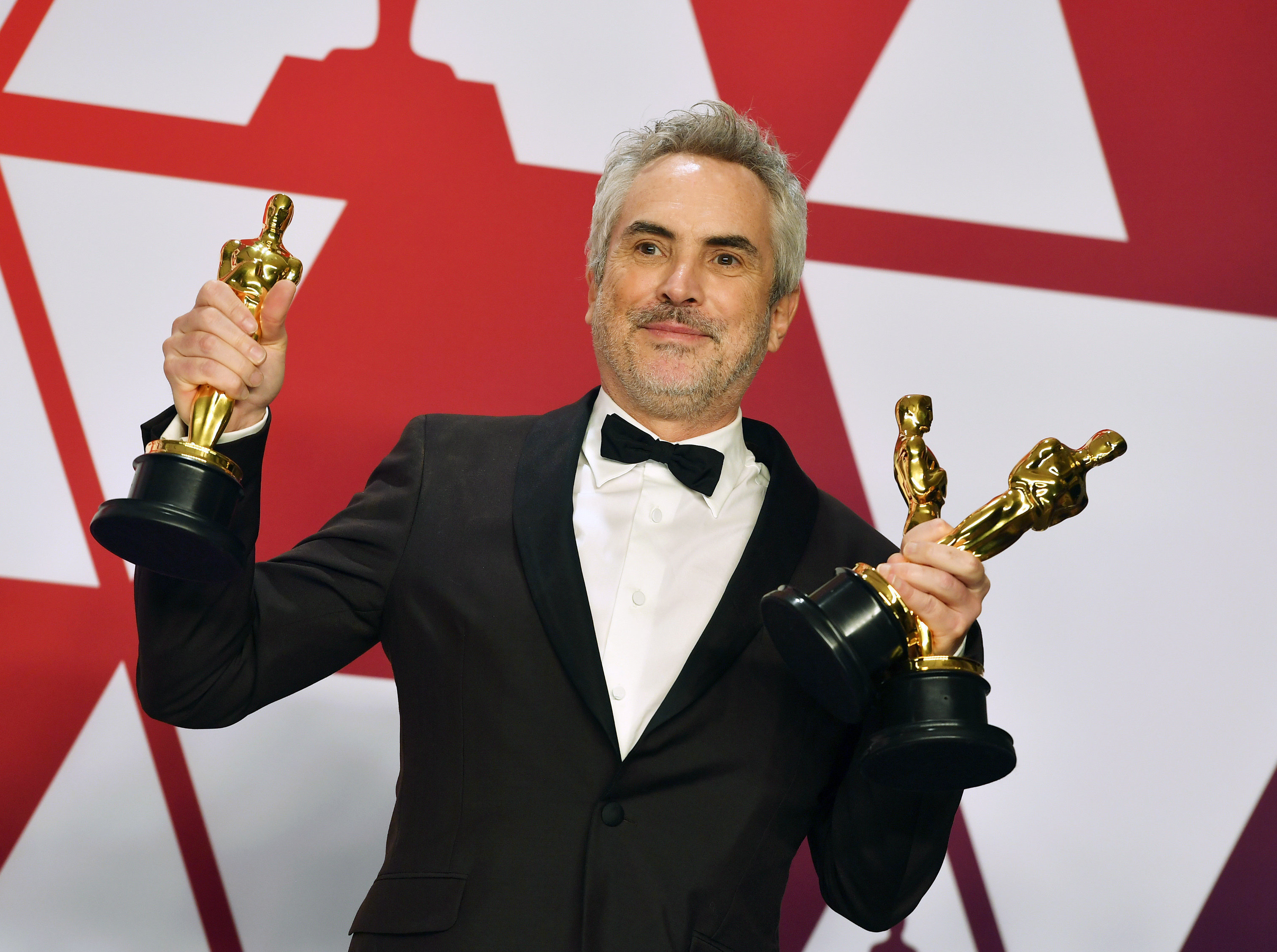 """""""Roma"""" director Alfonso Cuarón holding the film's three Oscars."""