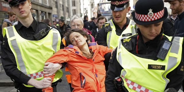 Police remove an Extinction Rebellion climate change protester who blocked a road outside the Goldman Sachs office in the City of London, Thursday, April 25, 2019.