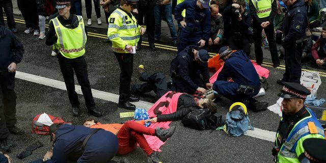 Extinction Rebellion climate change protesters are being removed from a road block by police, outside the Goldman Sachs International office in the City of London, Thursday, April 25, 2019. The non-violent protest group, Extinction Rebellion, is seeking negotiations with the government on its demand to make slowing climate change a top priority.