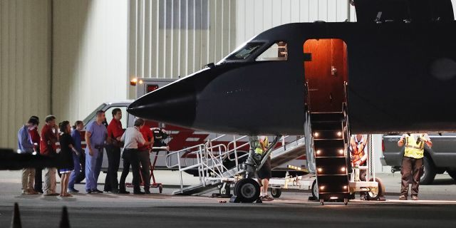 Medical personnel and visitors gather at the nose of a transport plane carrying Otto Warmbier at Lunken regional airport, Tuesday, June 13, 2017, in Cincinnati.