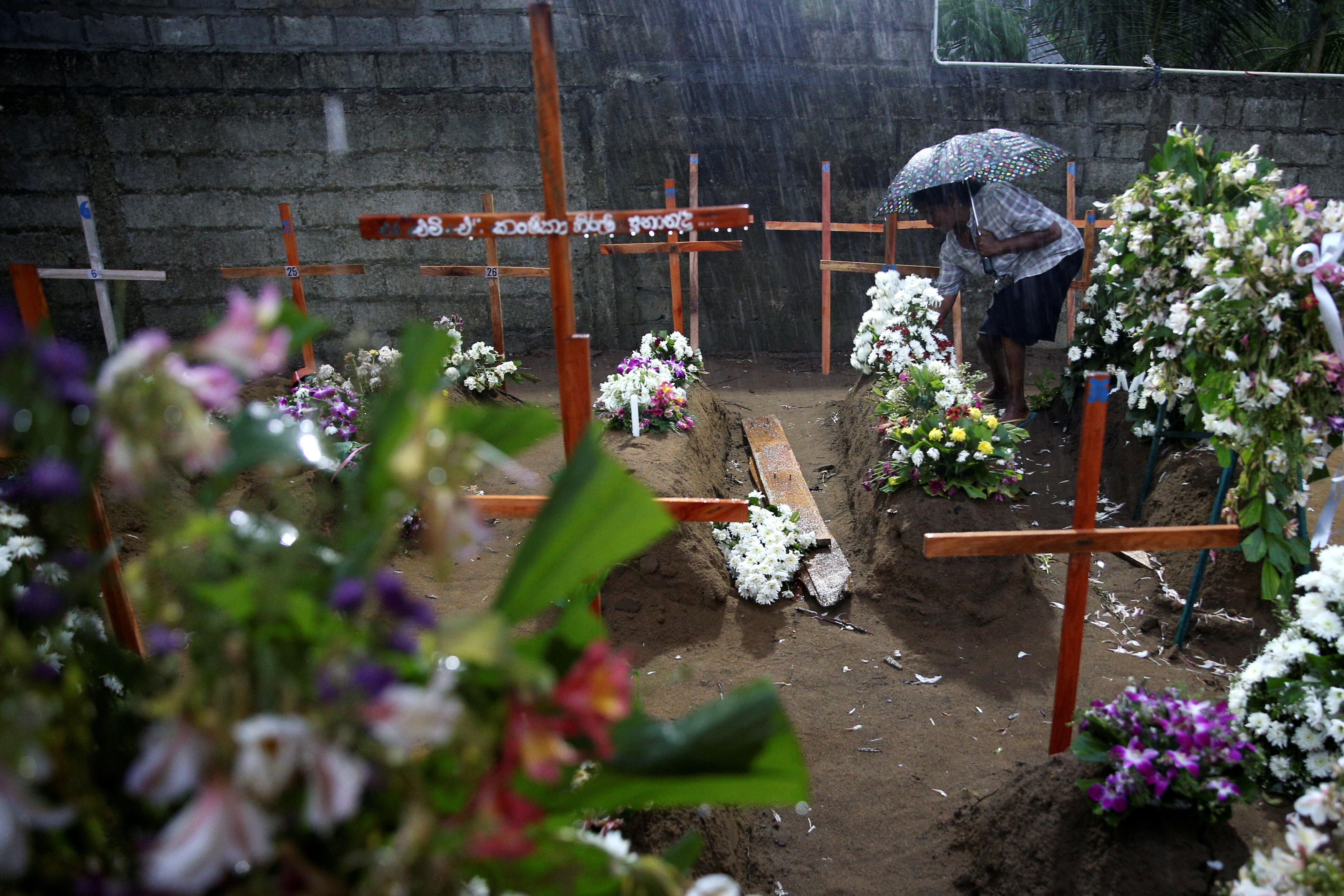 A woman comes to the site of a mass burial to pay her respects to the victims of a string of suicide bomb attacks on churches