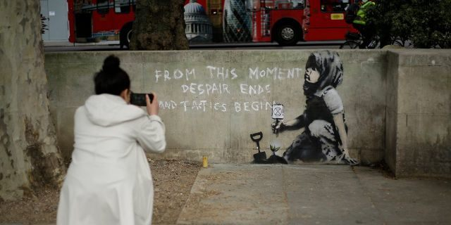 A woman takes a picture of a new piece of street art that people noticed for the first time last night and is believed to be by street artist Banksy on a wall where Extinction Rebellion climate protesters had set up a camp in Marble Arch, London, Friday, April 26, 2019.