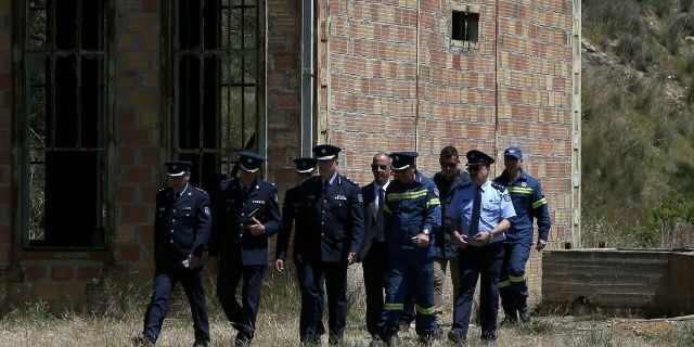 Chief of Cypriot police Zacharias Chrysostomou, center, walks with Cypriot investigators and police officers at a flooded mineshaft where two female bodies were found, outside of Mitsero village, near the capital Nicosia, Cyprus, Monday, April 22, 2019.