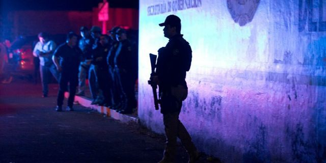 A Federal Police officer stands guard outside an immigration detention center in Tapachula, Chiapas state, Mexico, late Thursday, following a breakout.