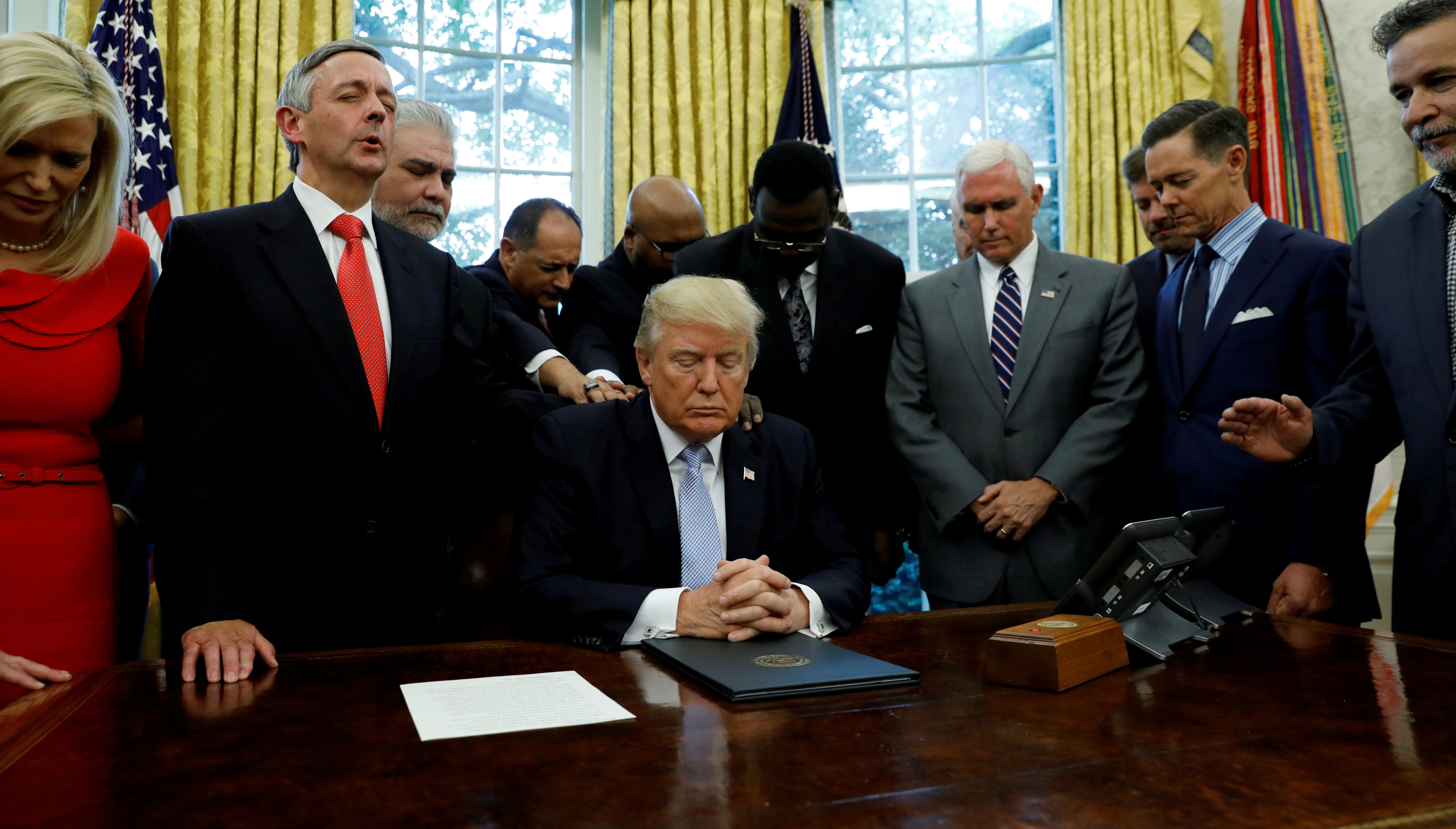 Faith leaders place their hands on the shoulders of President Donald Trump in the Oval Office as he takes part in a prayer on