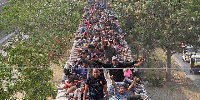 """Central American migrants, moving in a caravan through Juchitan, Oaxaca are pictured atop a train known as """"The Beast"""" while continuing their journey toward the United States, in Mexico April 26, 2019."""