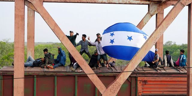 """Central American migrants hold Honduras' national flag, while moving in a caravan through Juchitan, Oaxaca atop a train known as """"The Beast"""" towards the United States, in Mexico April 26, 2019."""