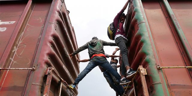 """Central American migrants hang on, as they ride a train known as """"The Beast"""", continuing their journey towards the United States, in Ixtepec, Mexico April 26, 2019."""