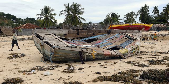 A young boy walks past a fishing boat that was destroyed when Cyclone Kenneth struck in Pemba city on the northeastern coast of Mozambique, Saturday, April, 27, 2019. (AP Photo/Tsvangirayi Mukwazhi)