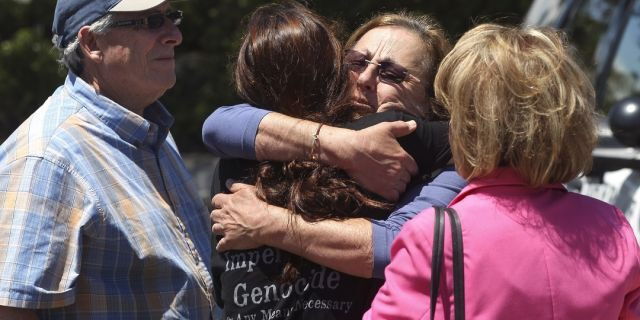 Members of the Chabad synagogue hug as they gather near the Altman Family Chabad Community Center, Saturday in Poway, Calif. (Associated Press)