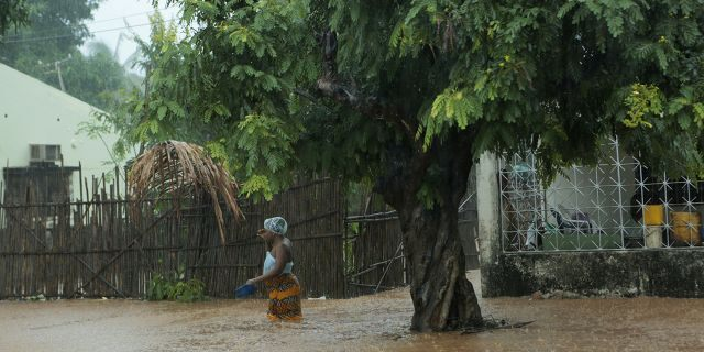 A woman walks through rising waters in Natite neighbourhood, in Pemba city on the northeastern coast of Mozambique, Sunday, April, 28, 2019.  (AP)