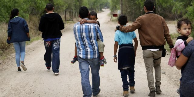 FILE - In this March 14, 2019, file photo, a group of migrant families walk from the Rio Grande, the river separating the U.S. and Mexico in Texas, near McAllen, Texas, right before being apprehended by Border Patrol. U.S. border authorities say they've started to increase the biometric data they take from children 13 years of age and younger, including fingerprints, despite privacy concerns and government policy intended to restrict what can be collected from migrant youth. (AP Photo/Eric Gay, File)