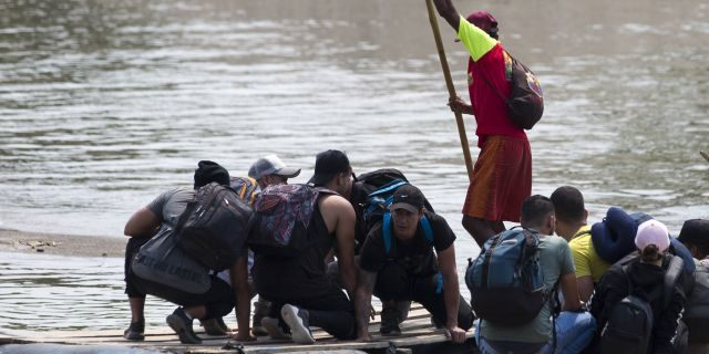 Migrants cross the border between Mexico and Guatemala, on a raft over the Suchiate river near Ciudad Hidalgo, Chiapas state, Mexico, Saturday, April 27, 2019. Thousands of migrants remain on the southern border of Mexico waiting for documents that allow them to stay legally in the country. (AP Photo/Moises Castillo)