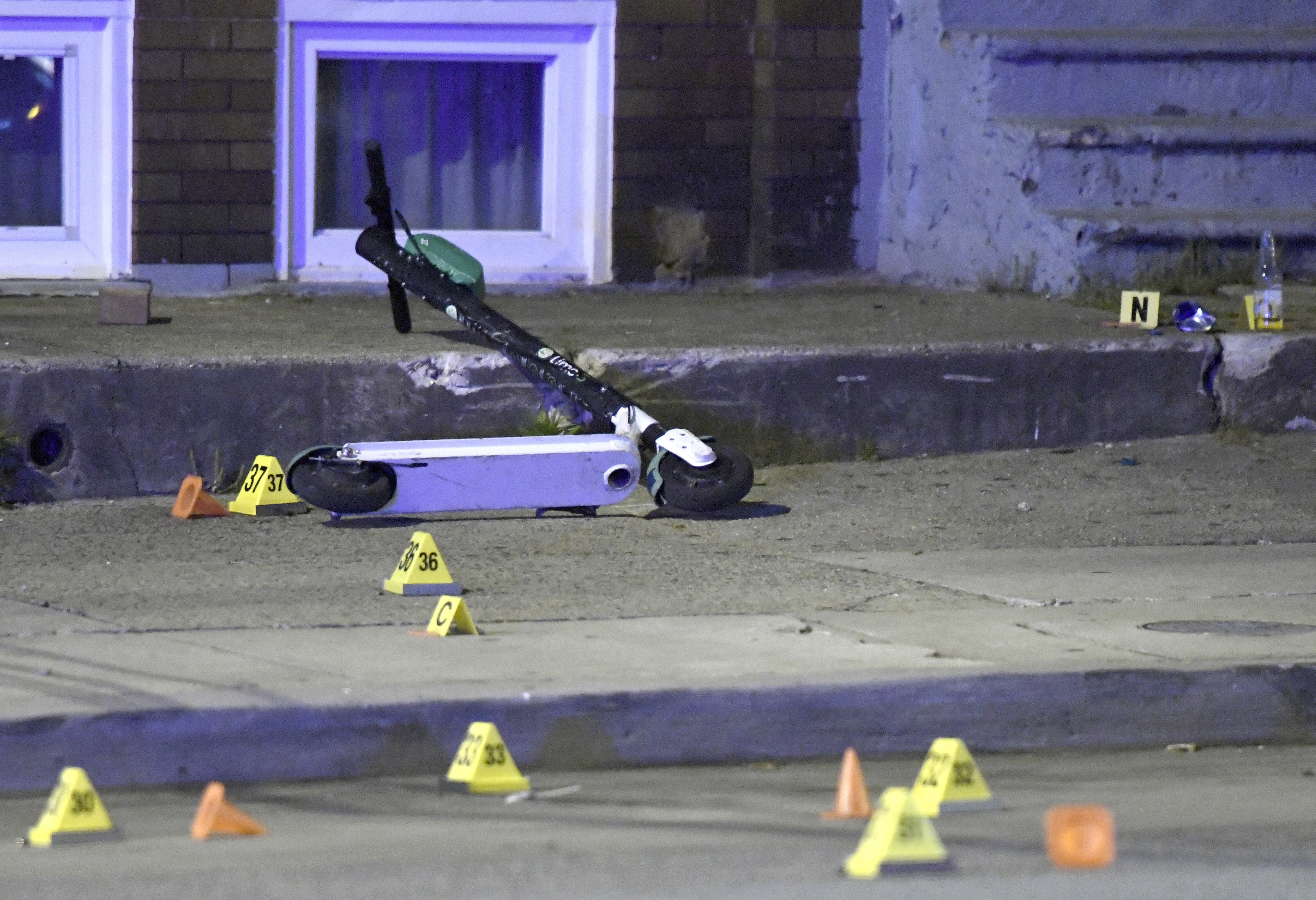 A scooter lies among evidence markers near the scene where authorities say eight people were shot, at least one fatally