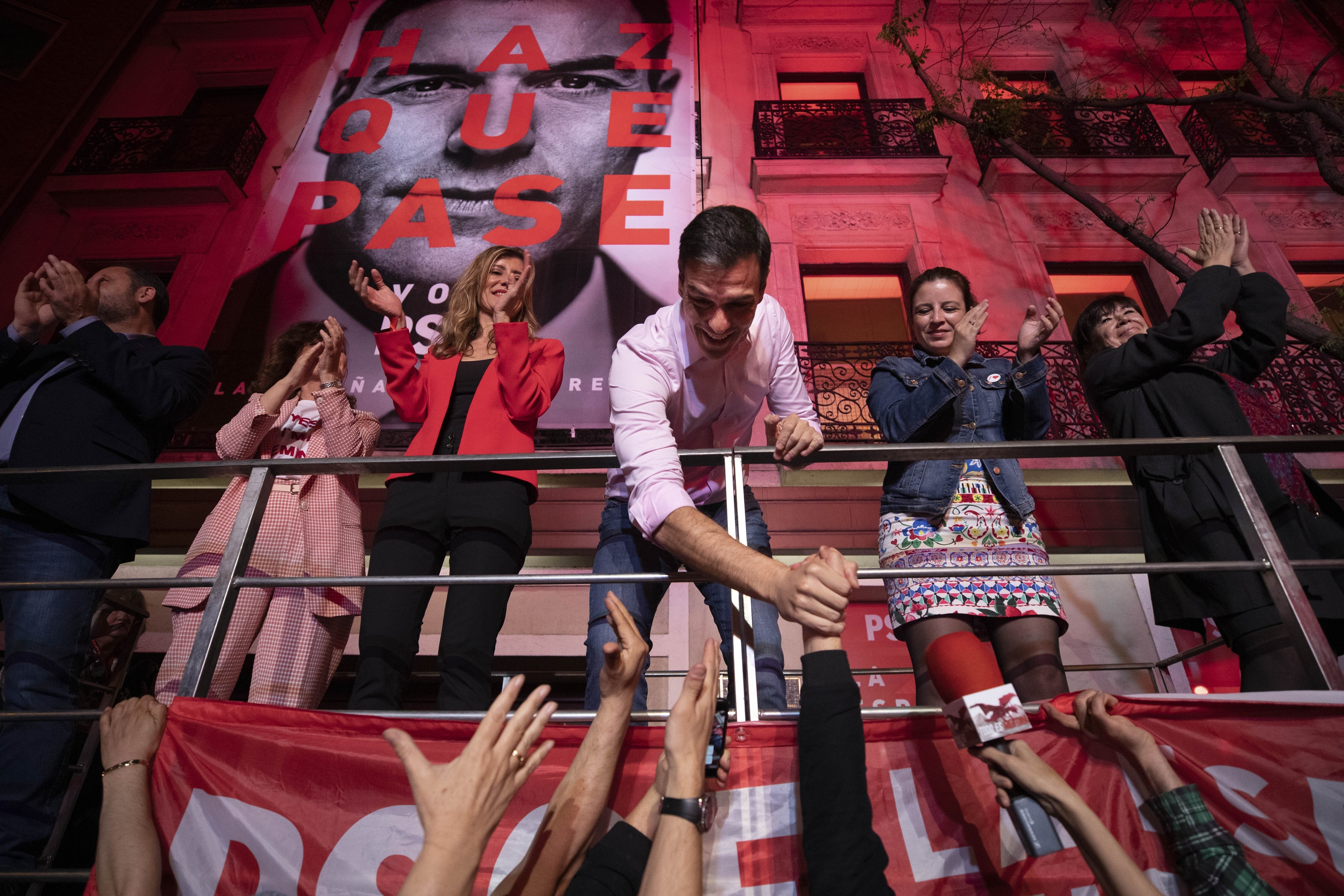 Socialist Party leader Pedro Sanchez shakes hands with supporters outside the party headquarters following the general electi