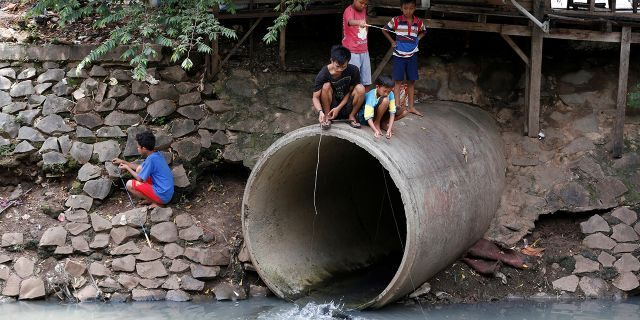 Children fish at a drainage pipe on a polluted canal in Jakarta, Indonesia November 18, 2016. Picture taken November 18, 2016.REUTERS/Darren Whiteside - S1BEUNQMJAAA