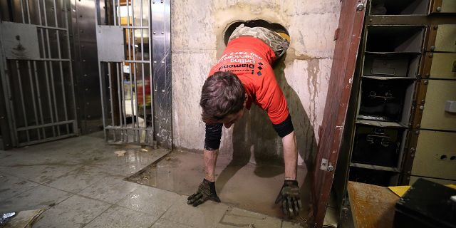 LONDON, ENGLAND - JANUARY 19: Diamond driller Sunny Kirby climbs through the hole used by burglars to access the underground vault of the Hatton Garden Safe Deposit Company which was raided in what has been called the largest burglary in English legal history on January 19, 2016 in London, England. Around 200 million GBP was stolen during the burglary which took place in April 2015. Four elderly men who were experienced thieves have since pled guilty to the crime while four other men are being tried on suspicion of involvement, one man, nicknamed 'Basil', is still at large. (Photo by Carl Court/ Hatton Garden Properties Ltd/Getty Images)