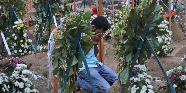 A Sri Lankan relative of a victim of Easter Sunday bomb blasts pays tribute at the burial site after a televised Sunday mass by Sri Lankan Archbishop Cardinal Malcolm Ranjith, in Negombo, north of Colombo, Sri Lanka. (AP Photo/Manish Swarup)