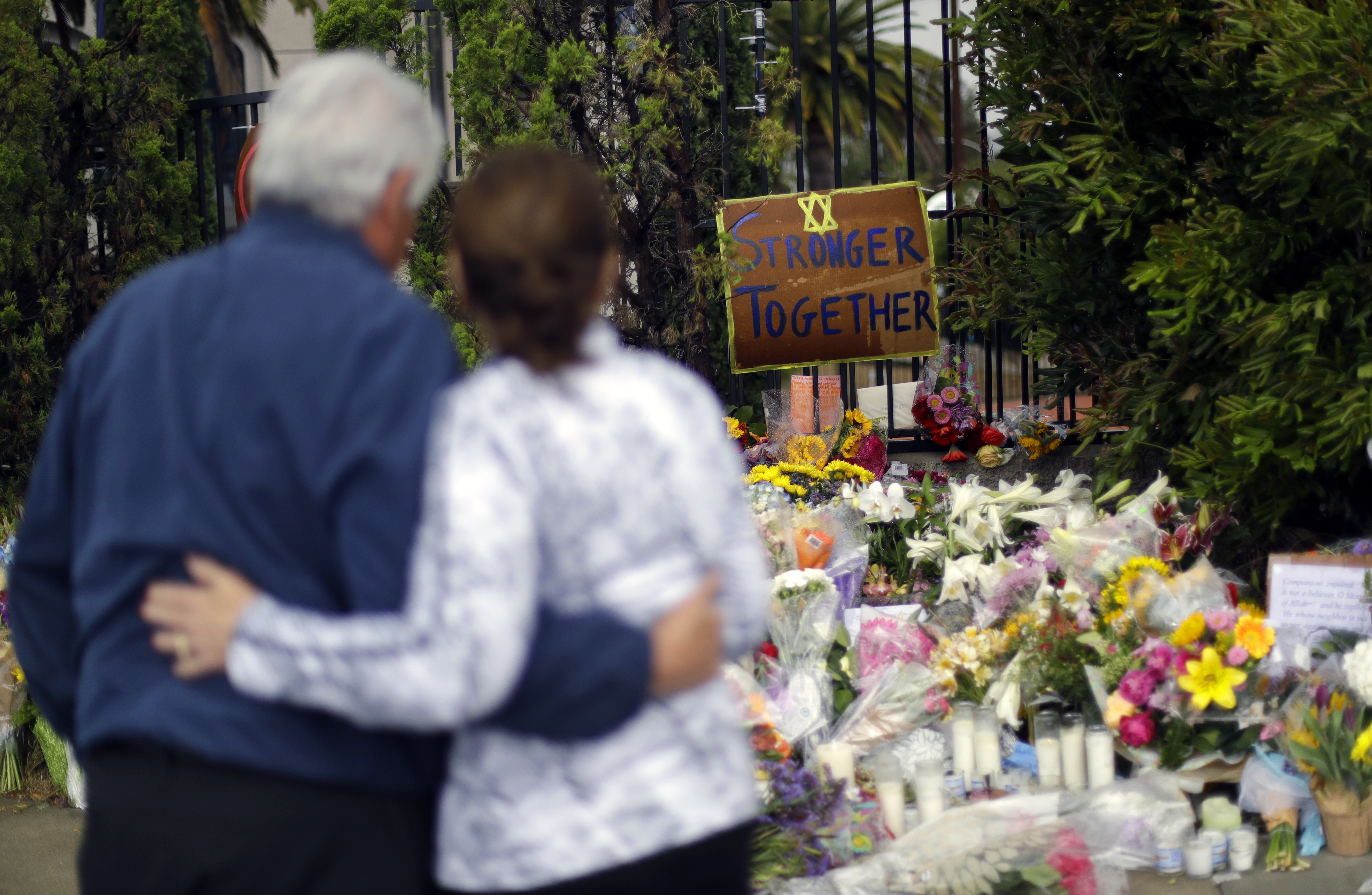 Two people embrace near a memorial across the street from the Chabad of Poway synagogue in Poway, California, on April 29, 20