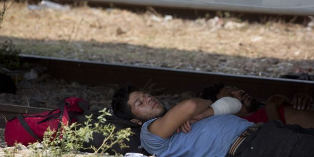 A Central American migrant takes a nap in the shade under a freight train car, last week in Oaxaca State, Mexico. (AP Photo/Moises Castillo)