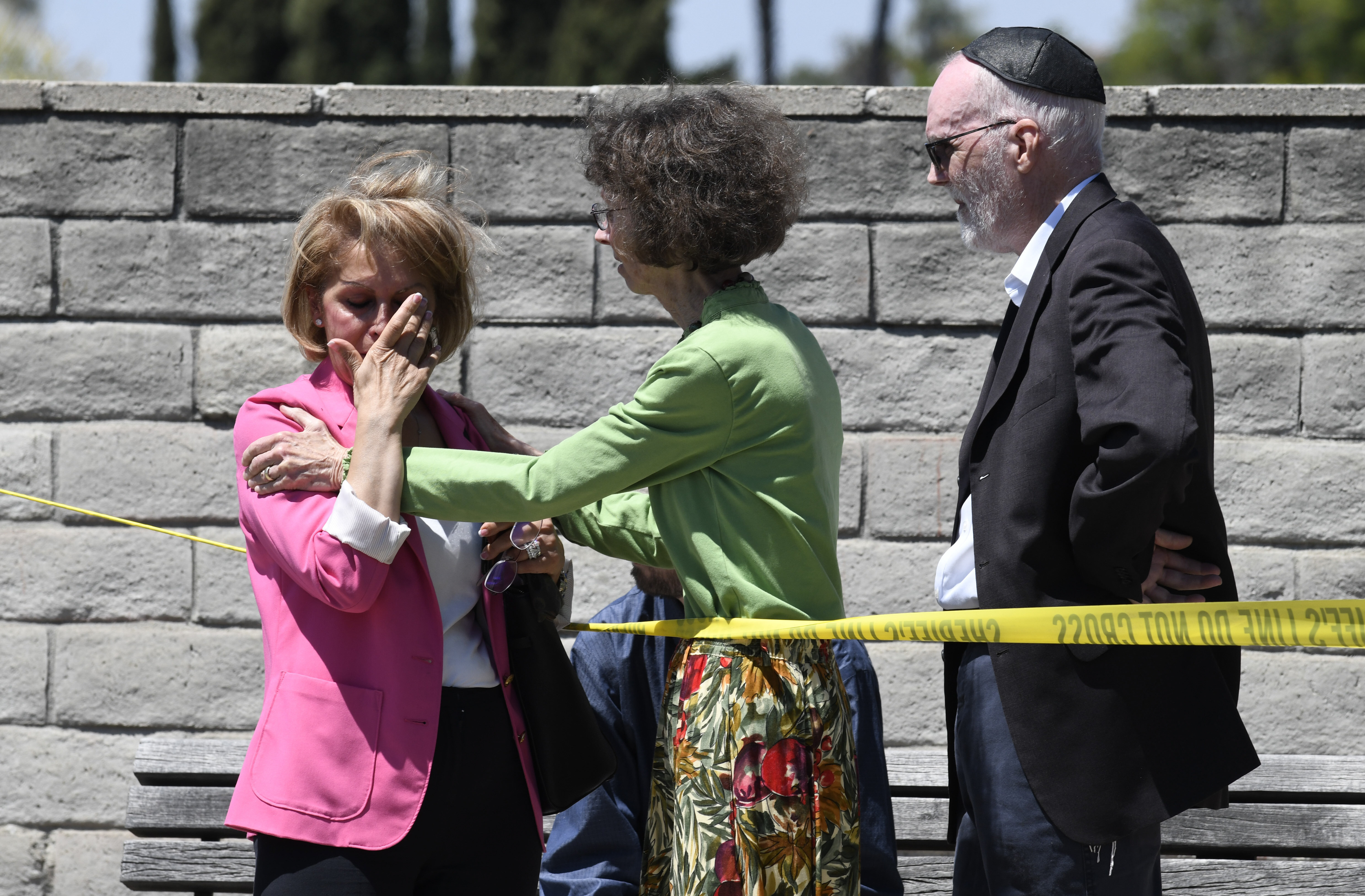 Synagogue members console one another outside of the Chabad of Poway Synagogue on Saturday after a gunman opened fire, killin