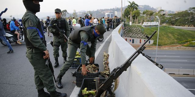 Soldiers take a position on an overpass next to the La Carlota air base in Caracas, Venezuela. (AP Photo/Ariana Cubillos)