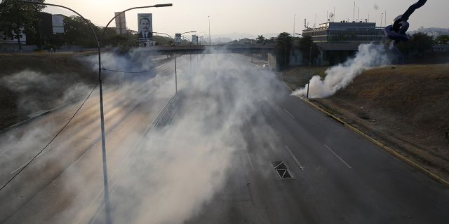 Tear gas covers an empty highway next to La Carlota air base in Caracas, Venezuela. (AP Photo/Ariana Cubillos)