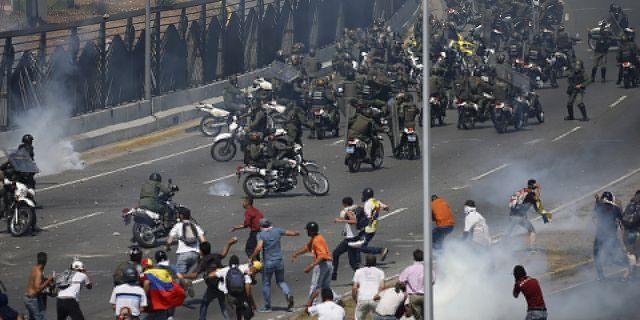Opponents to Venezuela's President Nicolas Maduro confront loyalist Bolivarian National Guard troops firing tear gas at them, outside La Carlota military airbase in Caracas, Venezuela, Tuesday, April 30, 2019. (AP Photo/Fernando Llano)