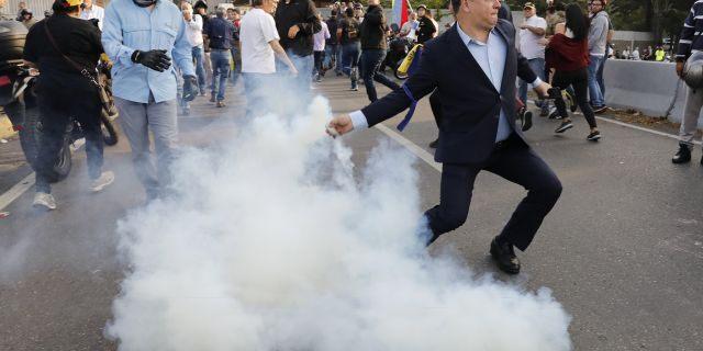 An opponent to Venezuela's President Nicolas Maduro returns a tear gas canister in Caracas, Venezuela, on Monday. (AP)
