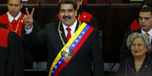 Venezuela's President Nicolas Maduro makes a victory sign during his swearing-in ceremony at the Supreme Court in Caracas, Venezuela, Thursday, Jan. 10, 2019.