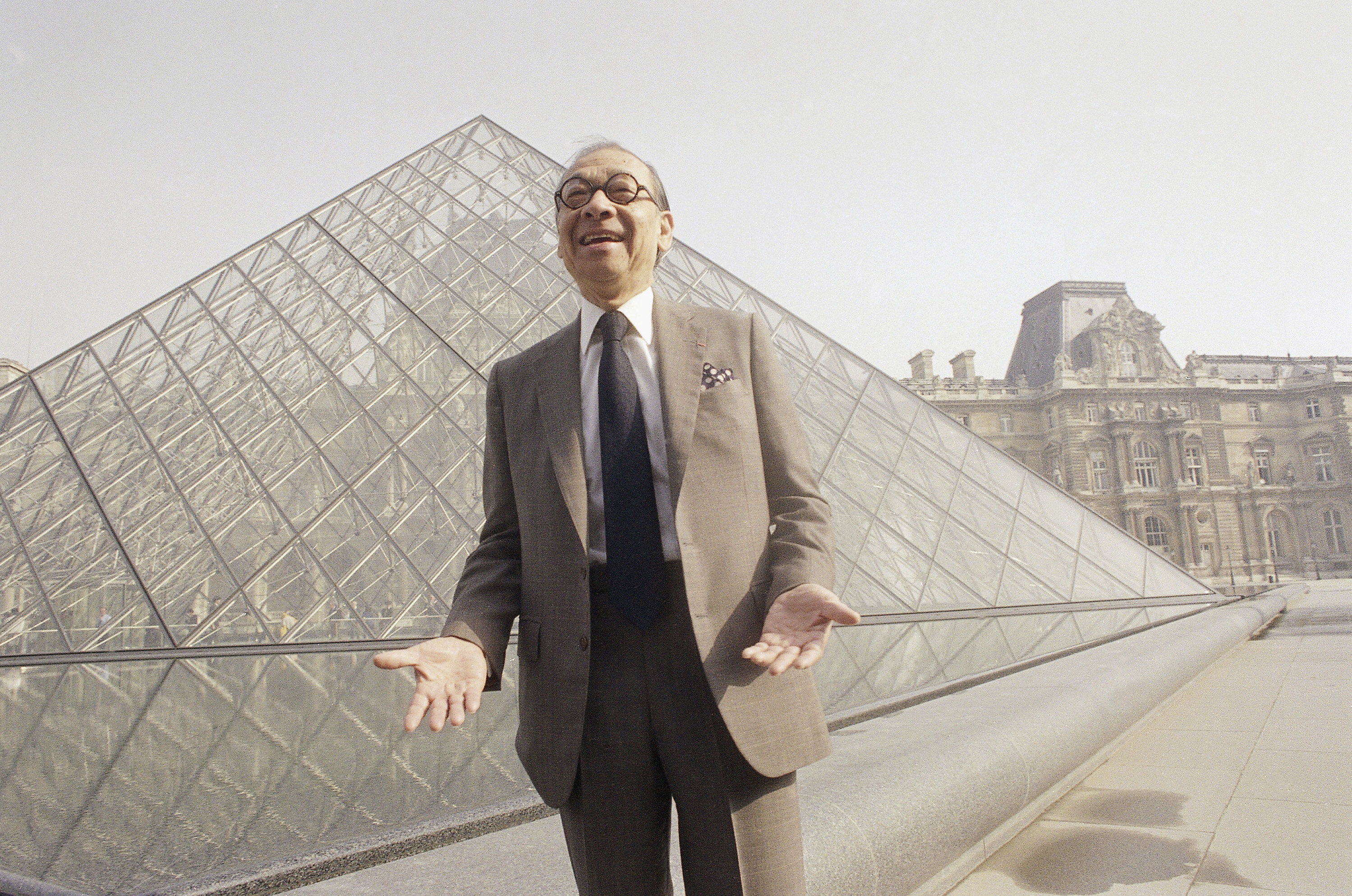 Chinese American architect I.M. Pei bursts out laughing while posing in front of the Louvre glass pyramid, prior to its inaug