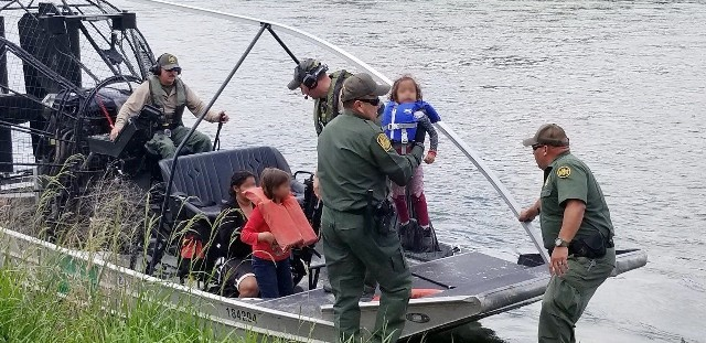 Del Rio Station marine agents transfer a rescued migrant family to ground-based agents for transportation after rescuing them from a stranded makeshift raft. (Photo: U.S. Border Patrol/Del Rio Sector)