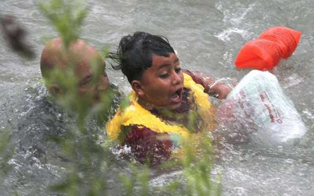 An Eagle Pass Border Patrol agents jumped into the Rio Grande to rescue a seven-year-old Honduran boy after he fall out of a makeshift raft. (Photo Bob Owen/San Antonio Express-News via AP)