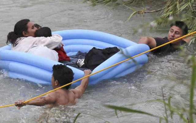 A migrant Honduran family struggles to reach the U.S. bank of the Rio Grande in a makeshift raft. (Photo Bob Owen/San Antonio Express-News via AP)