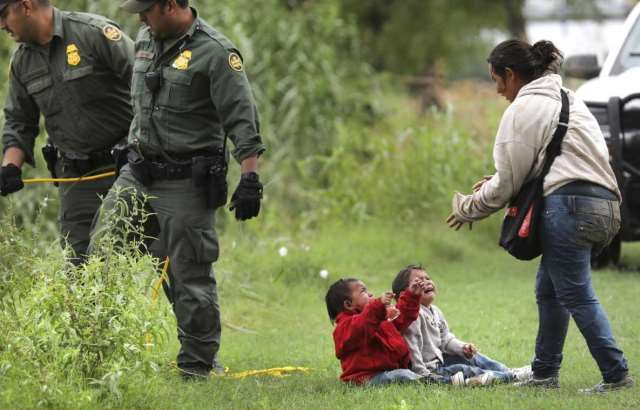 A Honduran mother runs to her crying babies after being rescued from a makeshift raft in the Rio Grande River. (Photo Bob Owen/San Antonio Express-News via AP)