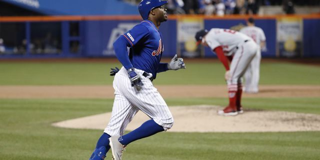 New York Mets' Rajai Davis, left, runs between third and home on his eighth-inning, three-run home run in the team's baseball game against the Washington Nationals, on Wednesday in New York, as Nationals relief pitcher Sean Doolittle, right, reacts on the mound. (Associated Press)